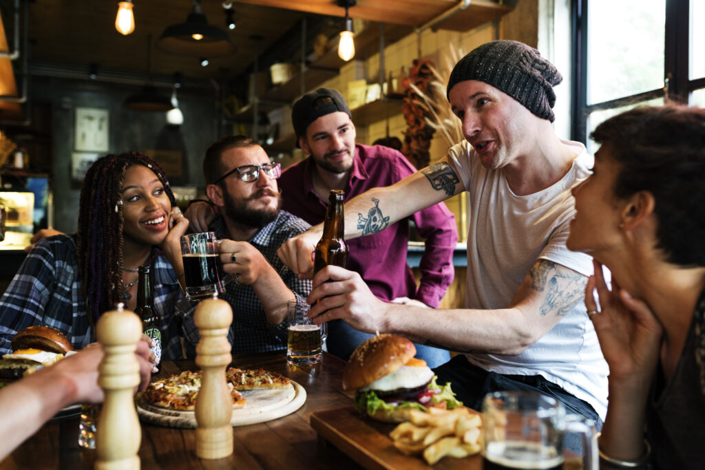 Picture of friends having fun eating and drinking in a bar